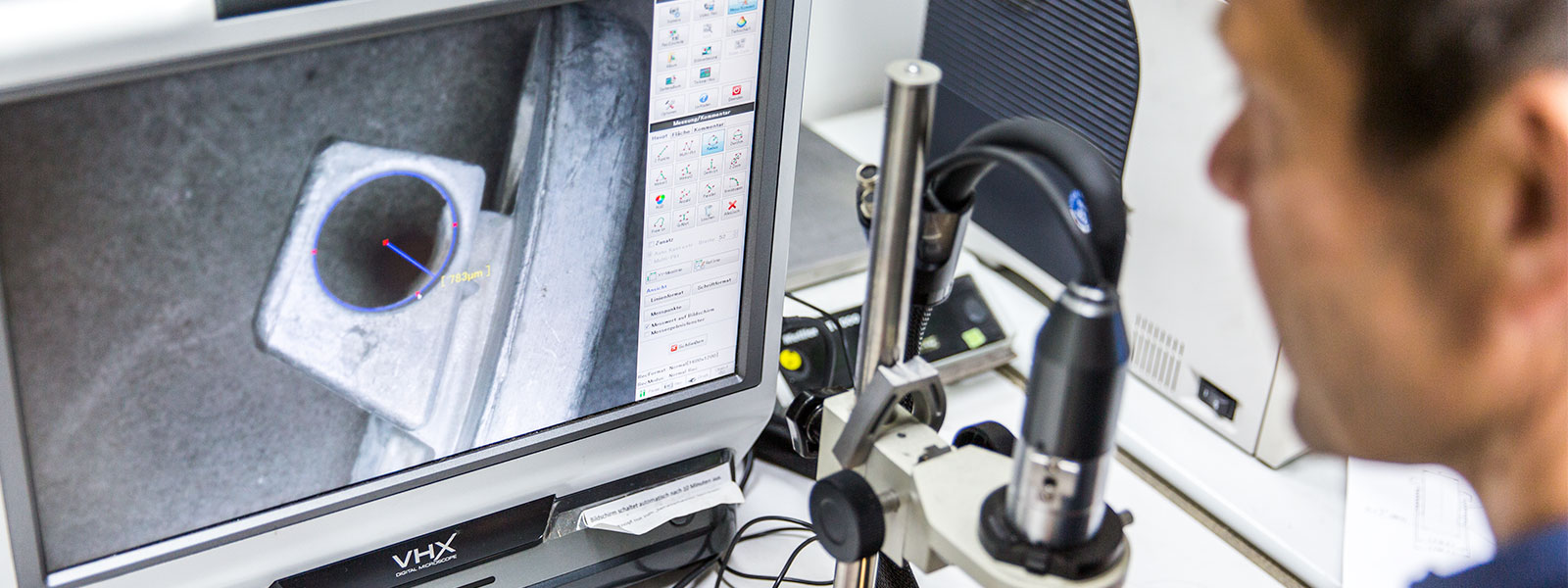 Employees performing microscopic analysis of the surface of a zinc die cast component